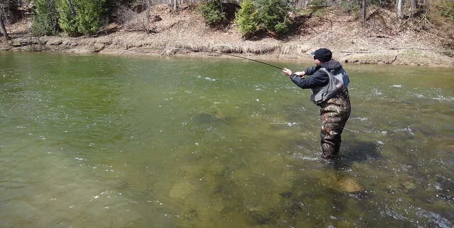 An angler fighting a steelhead while standing in the river with Neoprene waders on.
