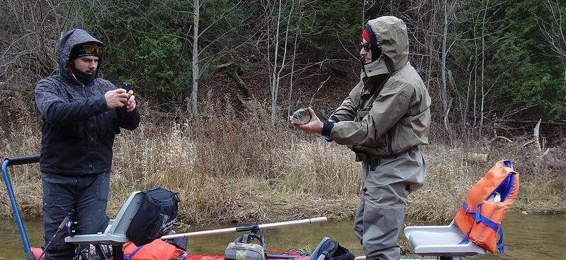2 anglers enjoying the rewards of trout fishing in the rain.