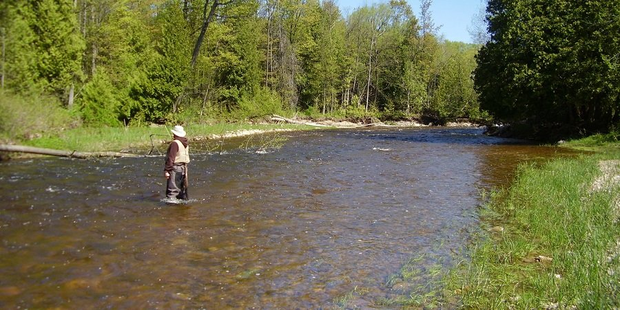 An angler using the right pound test leader for steelhead on a stained rivers
