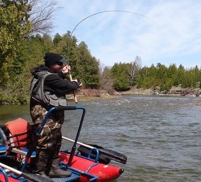 An angler fishing from a river boat